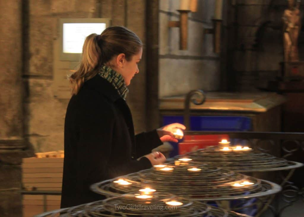 Becks lighting candles inside Notre Dame. There are three candle stands and each holds small lit tea candles.
